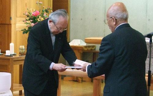賞状を受け取る一般社団法人日本福音ルーテル社団の長尾博吉常務理事(左)=29日、東京・池袋の日本福音ルーテル東京池袋教会で