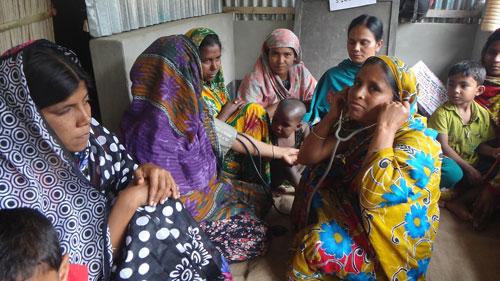 保護者の健康診断を行うスタッフ(写真:日本国際飢餓対策機構)