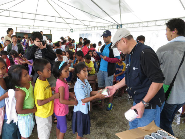 フィリピン台風で被災した子どもたちに「パンの缶詰」を手渡すパン・アキモトの秋元義彦社長(写真:日本国際飢餓対策機構提供)
