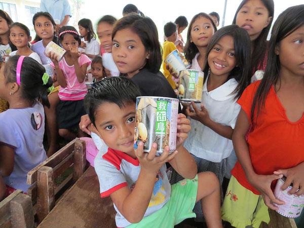 「パンの缶詰」を受け取ったフィリピンの子どもたち(写真:日本国際飢餓対策機構提供)