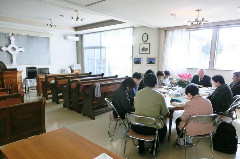 外は小雪の舞う朝、福島教会に集い、祈る人たち。歴史ある会堂を失い、隣地に残った集会所での祈祷会=6日