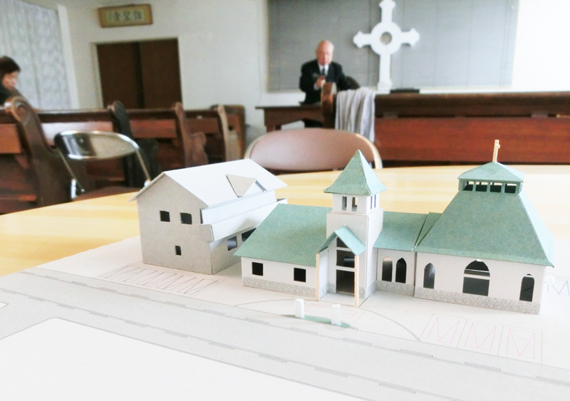 新会堂の建築模型はすでにできあがっている。写真奥は講壇に立つ似田牧師=6日、福島教会の伝道館で
