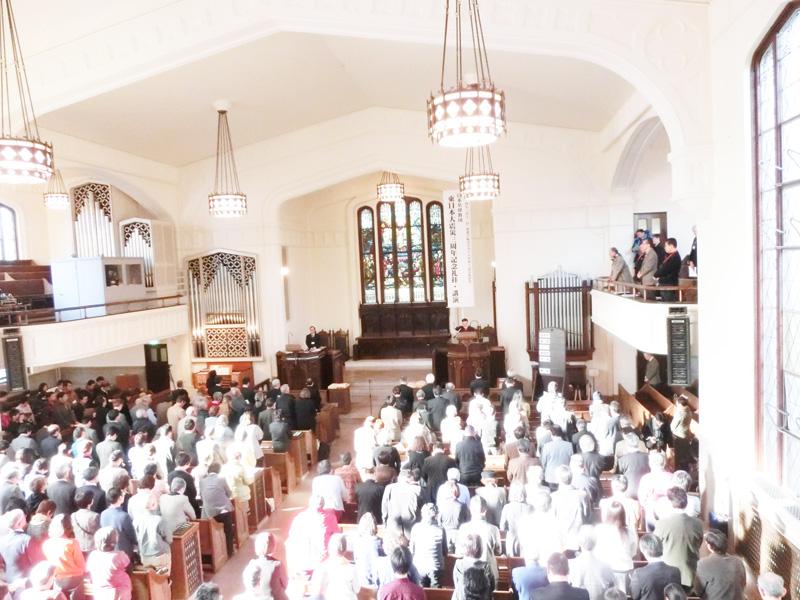 全国から多くの人が祈りのために東北に集った。壇上は祈祷する高橋和人・仙台東六番丁教会牧師=11日、仙台市、東北学院大学ラーハウザー記念礼拝堂で