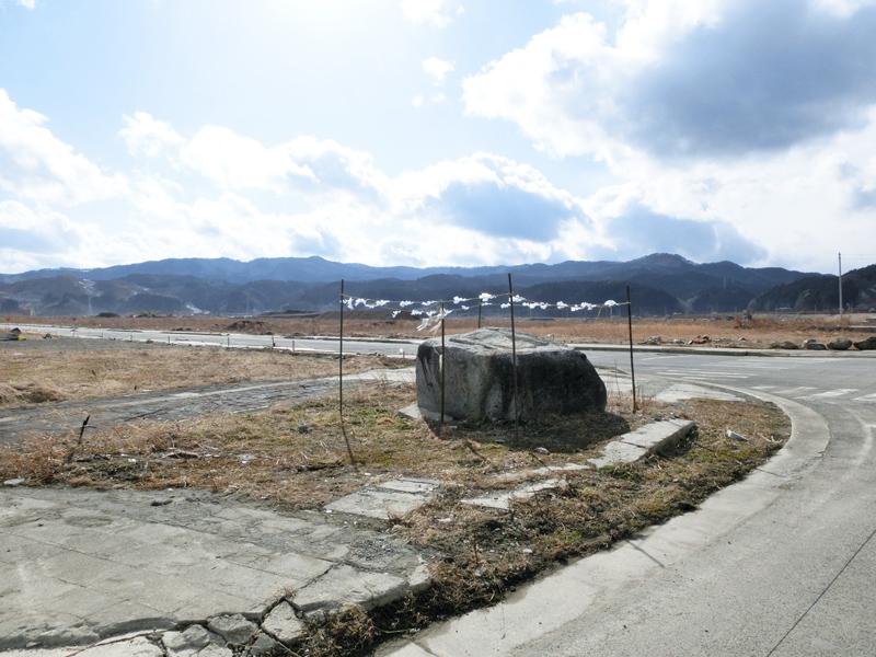 津波で消失した市街地に残された石。かつて神社として祀られ、今は注連縄と紙垂で飾り付けられている。