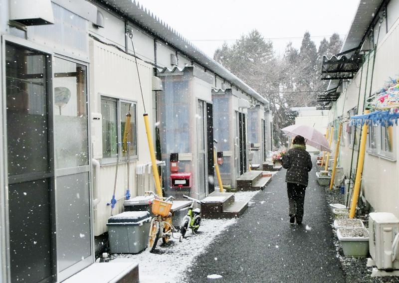 雪の降るなか、仮設住宅の各戸に花を届けるボランティアの女性。こうした訪問は、高齢者の安否確認にもなっている。