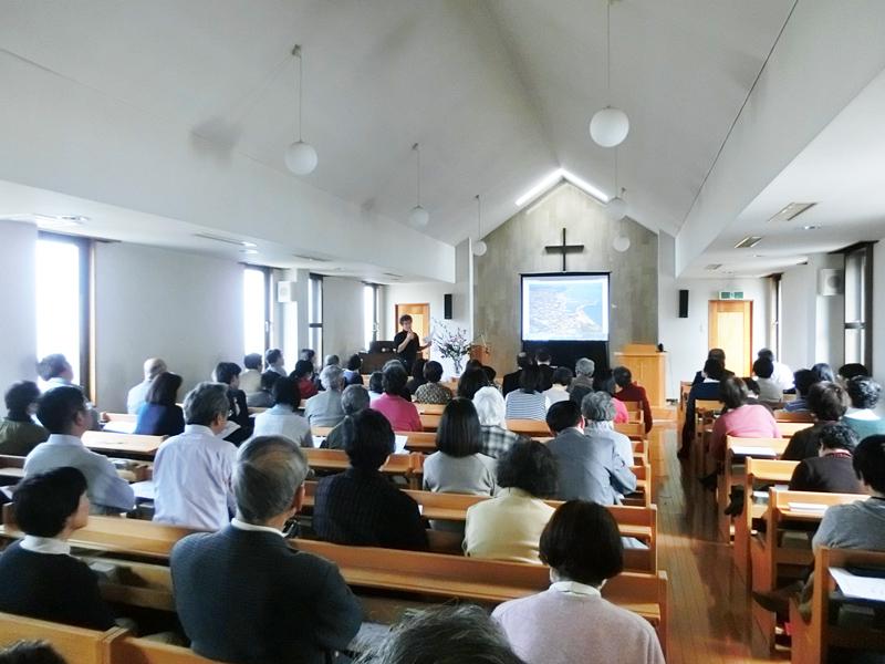 写真をスクリーンに映して被災地と支援の様子を伝える松本さん=23日、東京・石神井教会で