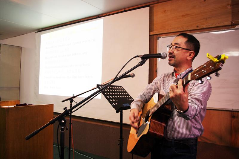 ギターを弾きながら3カ国語で歌う風間牧師