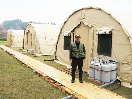 サマリタンズ・パースが岩手県住田町に設営した仮設テントの前に立つディビッド風間氏=2011年4月