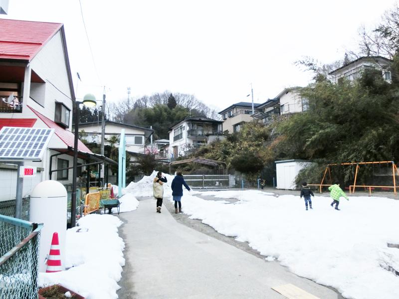 二本松幼稚園の庭で遊ぶ子と、迎えに訪れた母親たち。左に見えるのはソーラーパネルつきの放射能測定器。