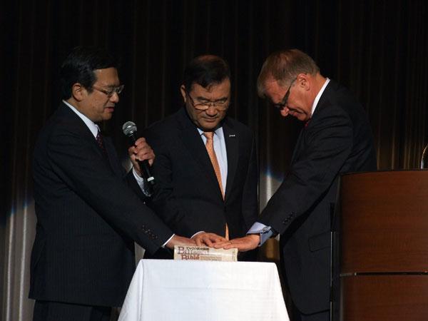 聖書に手を置き、日本とアメリカ、そして韓国の調和と協力の実現を求め祈る、左から日本CBMC会長の井上義朗氏、CBMCアジア会長のキム・チャンソン氏、CBMC国際会長のジェームス・D・ファンスタール氏