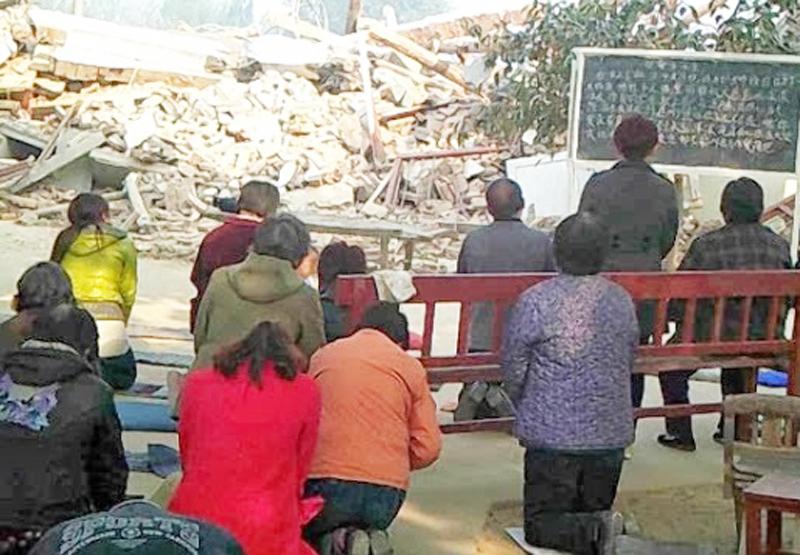 取り壊された教会とその前で祈る信徒たち。場所や教会の名は明らかにされていない。(写真:chinaaid)