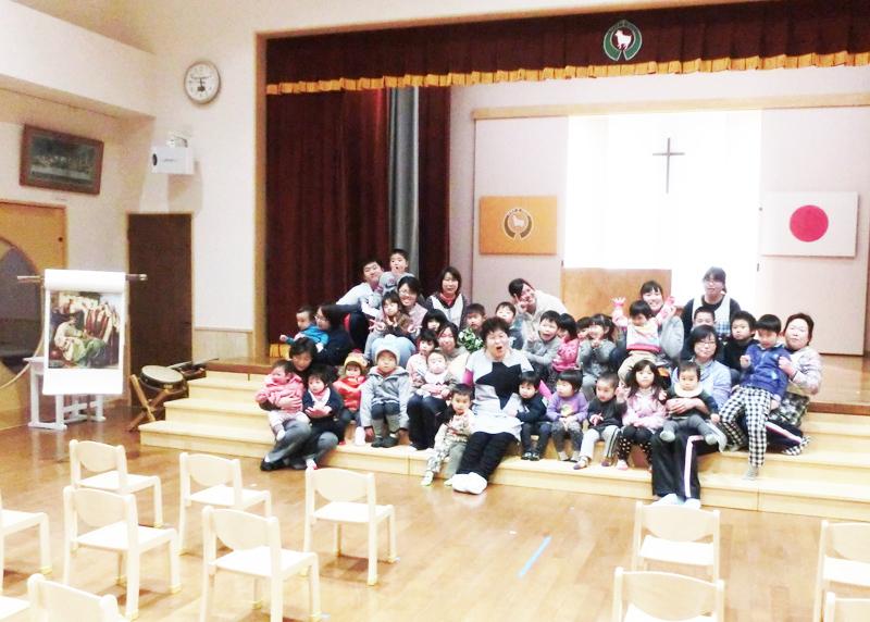 堀園長を囲む園児たち。毎週月曜日に十字架のある遊戯室で聖書のお話をする。
