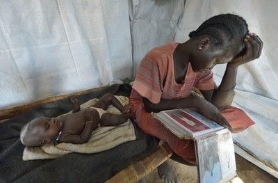 南スーダン北部国境付近のアジョウン・ソクという地域の近くにある仮の避難所で赤ん坊が眠る間に親戚の写真を眺めるニャンセム・マヨルさん。故郷の町ベンティエウで2013年の暮れに戦闘が勃発した後、彼女たちはここへ逃げてきた。(写真:ACT / Paul Jeffrey)