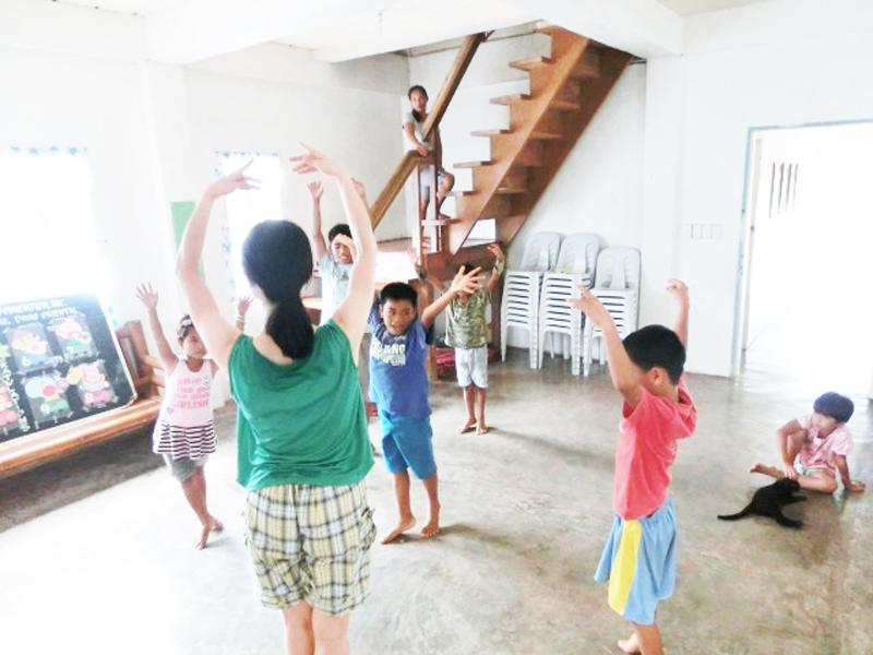 ビジターの日本人女性からバレエを教わる。初めて目にする動きをまねて指導に耳を傾ける子どもたち。