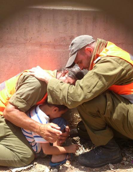 ハマスによるロケット弾攻撃中、4歳の子どもを体を張って守るイスラエル国防軍の兵士ら=7月15日(写真:Israel Defense Forces / Li Aviv Dadon)<br />