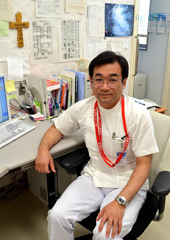十字架を見上げて診察に当たる宇田川雅彦医師。千葉県船橋市医療センターの精神科医は宇田川氏1人。急患、外来、入院患者を全て1人で診察している。