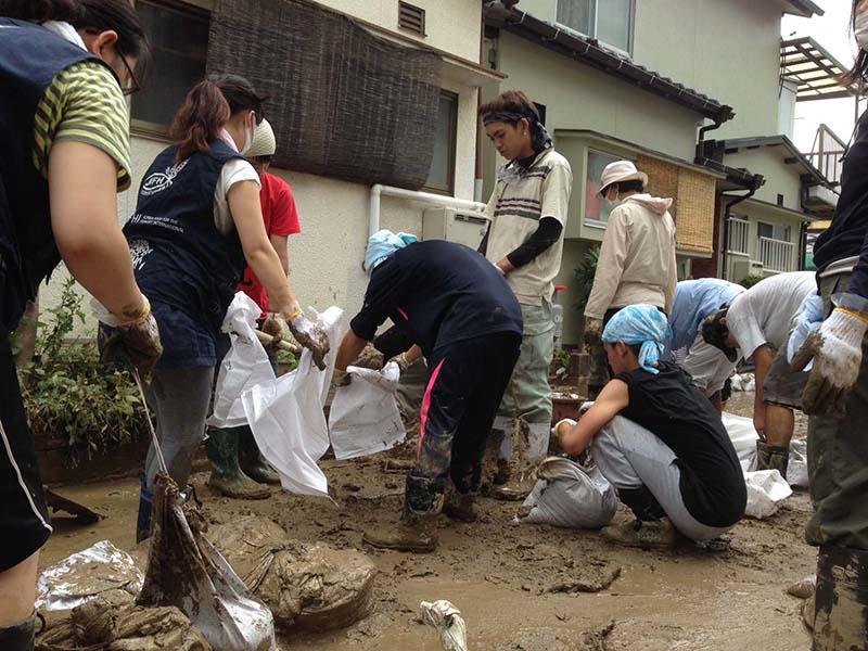 泥出し作業をするボランティアたち(写真:日本国際飢餓対策機構)<br />