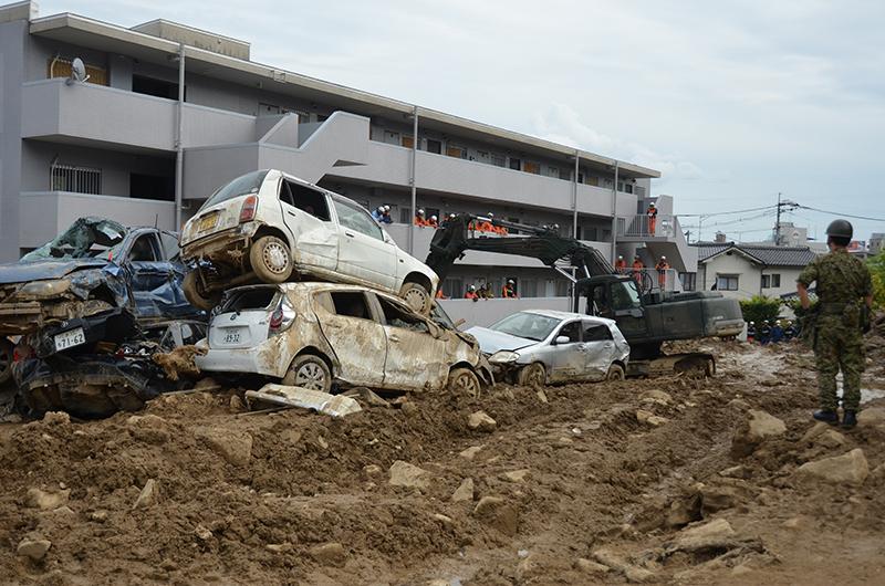 1階が土砂で埋もれたマンション前で自衛隊、消防、警察が合同で捜索を行なっている。(写真:日本国際飢餓対策機構)<br />