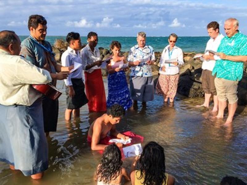 キリスト教徒のグループが海の中で祈り、海面上昇による悪影響を受けている社会との連帯を表している。(写真:Samoa Observer)