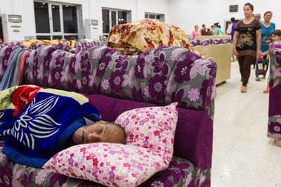 間に合わせの共同寝室で休む、イラク北部のカラコシュから避難してきた障がいを負った男性。イラク北部の都市ドホークにある、東の聖ペテロ・パウロ古代アッシリア教会で(写真:世界教会協議会 / グレッグ・ブレッケ)