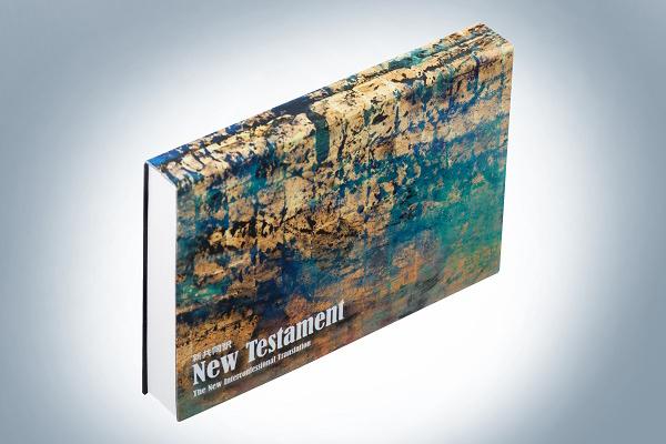 新発売された『新共同訳 新約聖書 フリップバック装』。表紙は、ホワイトハウスの文化担当顧問を務めた経験のあるマコト・フジムラ氏の作品「Golden Sea」が使用されている。(写真:日本聖書協会提供)<br />