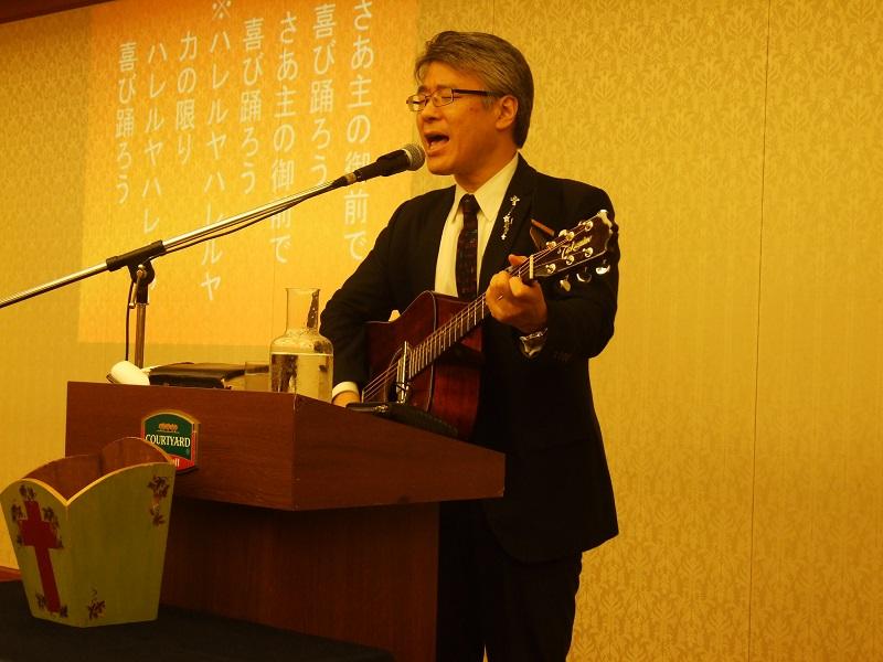 自らギターを弾いて賛美する万代栄嗣牧師=22日、銀座東武ホテル(東京都中央区)で