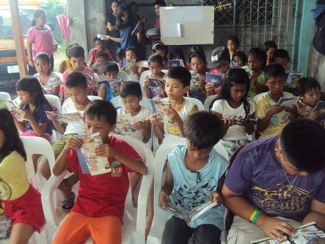 マンガ聖書を熱心に読み入る子どもたち。新生宣教団は今回、マンガ聖書など教会学校用の教材5千セットをフィリピンへ送った。