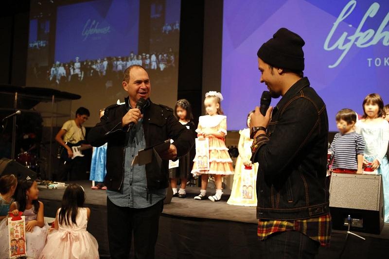 子どもたちを祝福するライフハウスのロド・プラマー主任牧師(左)と通訳の佐藤カービー氏=2日、ライフハウス(東京・六本木)で