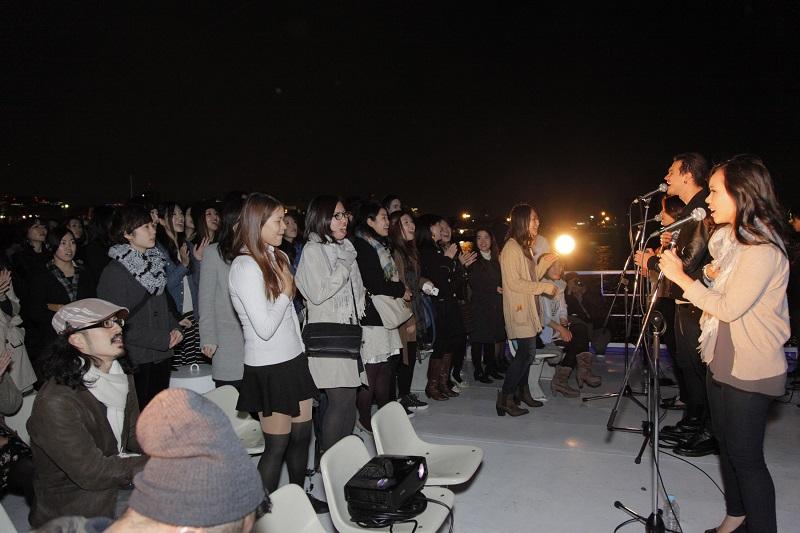 賛美の風景。約200人が集まり、お台場の夜景をバックにシックな雰囲気で神を賛美した=8日、東京・お台場で