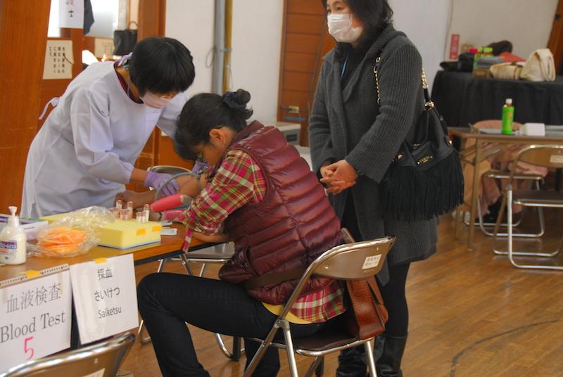 血液検査のために採血を受ける仮放免者。その横で通訳が見守る=11月30日、カトリック高崎教会(群馬県高崎市)で