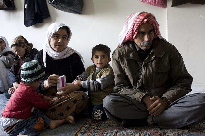 イスラム国に襲撃されたイラク北西部の村から逃れてきた家族。家族の唯一の稼ぎ頭であったサイードさん(23)は、ヤジディ教の武装グループ「ヤジディ・クルド」のメンバーで、逃げ遅れた人々を助けようと村に戻ろうとしたところを殺された。サイードさんの妻であるカリリさんは、幼い3人の子どもと共に取り残され、トルコ南東部の町シュルナクにある暖房のないむき出しの建物で、親戚ら16人と共に避難生活をしている。(写真:Caroline Gluck / EU / ECHO)