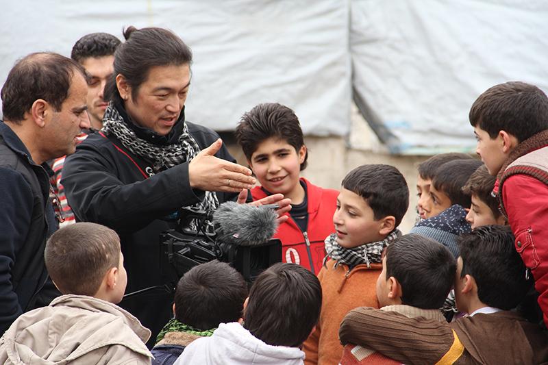 トルコとの国境に近いシリア北部の都市アレッポでの取材で、子どもたちに囲まれている後藤健二さん(写真:インディペンデンド・プレス)<br />