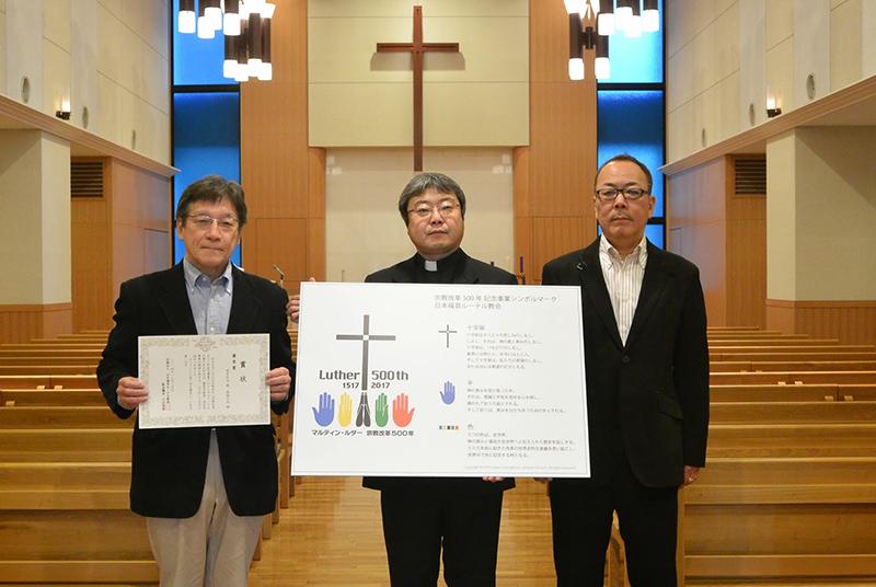 受賞者の坂本信也さん(左)と南端久也さん(右)。中央は、日本福音ルーテル教会西教区長の滝田浩之牧師=2014年12月25日、日本福音ルーテル大阪教会礼拝堂(大阪市)で(写真:日本福音ルーテル教会提供)