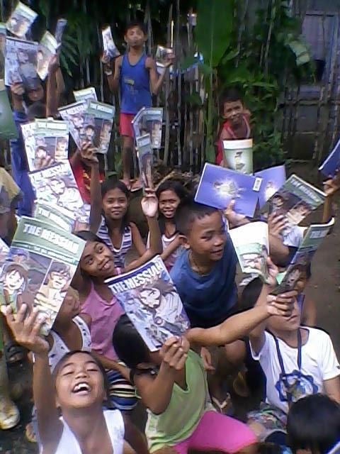 マンガのテキストを手にして喜ぶ子どもたち(写真:新生宣教団提供)<br />
