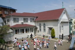 国の登録有形文化財に指定されている日本基督教団横須賀上町教会。付属のめぐみ幼稚園で園児たちが遊んでいる=同教会提供