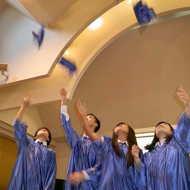 シオン・クリスチャン国際学校の第1期卒業生となった4人。4月から、2人は日本の大学へ、1人は6月に渡米し、そのまま米国の大学に進学するか、来年日本の大学を受験するか決めるという。またもう1人は、同校のスタッフとして働くことになる。卒業生が身に着けているガウンは卒業式のために米国から取り寄せたという=13日、小岩四恩キリスト教会(東京都葛飾区)で(写真:同校提供)