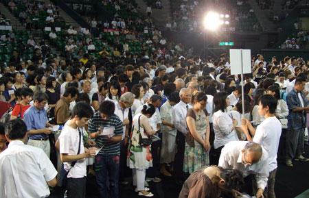 2日間で延べ8000人が参加した「日本クリストファー・サン国際大会2010」で、信仰の決心をしてステージ前に進み出る参加者=2010年9月4日、有明コロシアム(東京都江東区)で(写真:クリストファー・サン伝道協会提供)