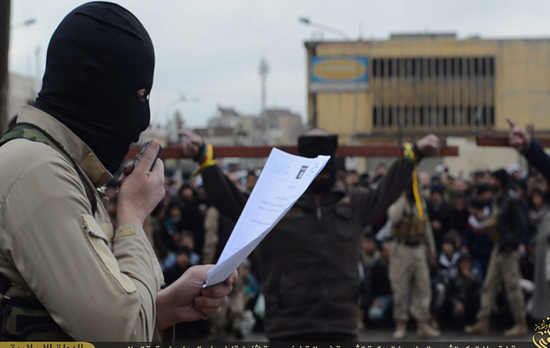 「イスラム国」(IS)が実行支配するイラク北部のモスルで、十字架に縛り付けられた2人の男性の前で罪状を読み上げる、覆面したIS戦闘員。このあと2人は、山賊行為を理由に後頭部を銃で撃たれ処刑された。(写真:「Justpasta.it」のスクリーンショット)