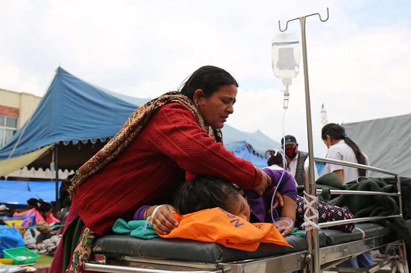 ネパールの首都カトマンズにあるトリブバン大学付属病院で、けがを負った娘に付き添う母親=26日(© UNICEF / NYHQ2015-1013 / Nybo)