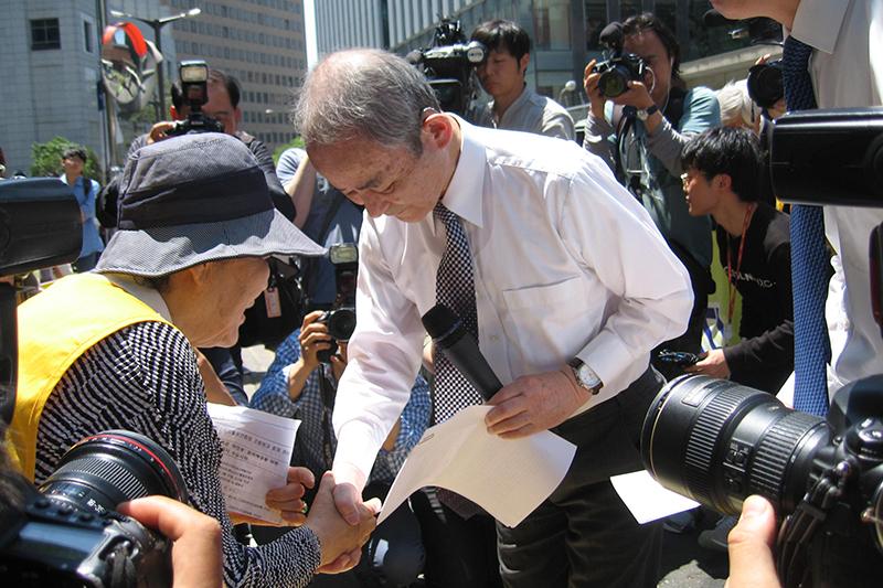 水曜集会で謝罪文を手渡し、元従軍「慰安婦」の李容洙(イ・ヨンス)さんと握手する村岡崇光(たかみつ)氏=27日、韓国・ソウルの日本大使館前で