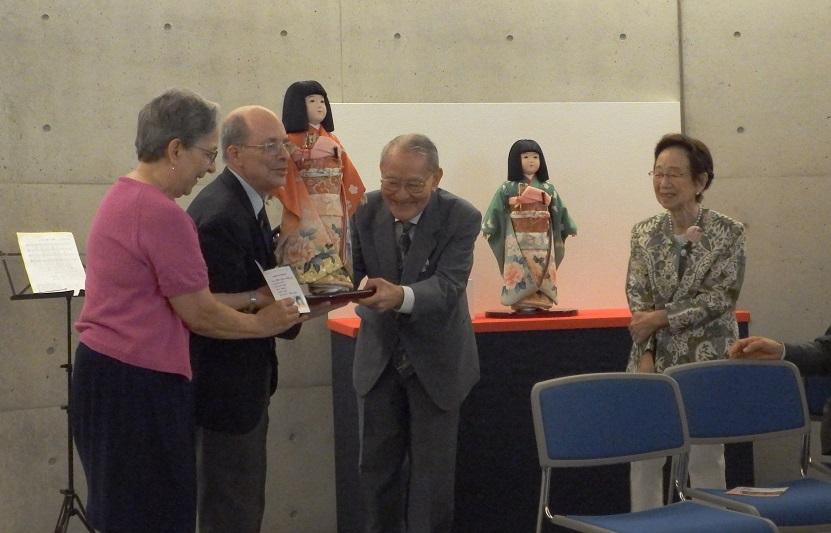 渋沢雅英さん(中央右)から、「渋沢さくら」と名付けれらた市松人形を受けとるシドニー・ギューリック3世(中央左)=5月30日、渋沢史料館(東京都北区)で