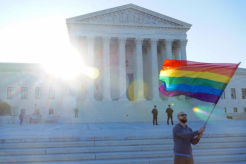 米連邦最高裁判所前でLGBTら性的少数者支持を象徴するレインボーフラッグを掲げる男性=4月28日(写真:Ted Eytan)