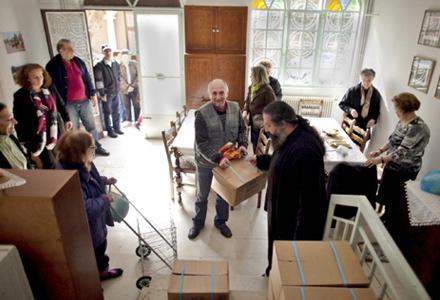 豆やパスタ、缶入り牛乳といった品物からなる1カ月分の配給がいっぱい詰まった食品の小包を受け取るため、順番を辛抱強く待つアテネの住民。アテネのフィロパポスにある教会「アギオス・ニコラス」の公民館は、国際正教慈善協会(IOCC)と、ギリシャ正教会の人道支援部門「アポストリ」が、貧しい家庭へ食料の小包を配布するために使っている場所のうちの一つ。(写真:IOCC / Eirini Vourloumis)