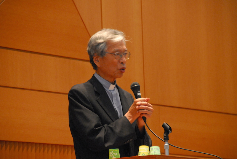 日本弁護士連合会主催のシンポジウムのリレートークで「強行採決は大変残念」と語る岡田大司教=15日、弁護士会館(東京都千代田区)で