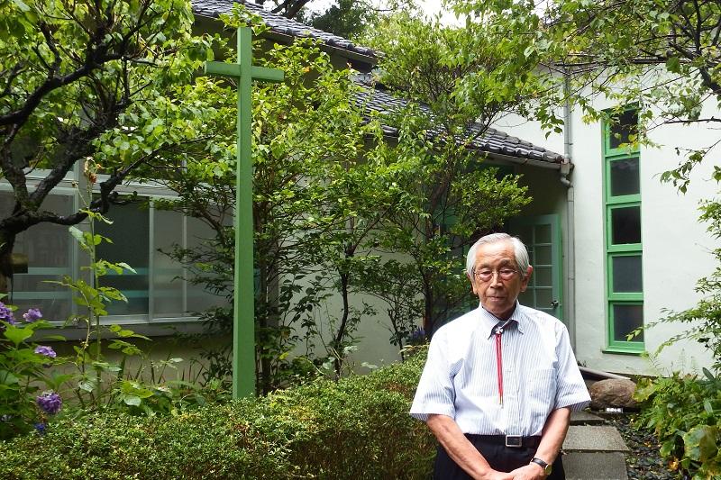 キリスト教学校教育に約60年携わってきた、聖ステパノ学園理事長で同園小学校・中学校校長の小川正夫さん。同学園に建てられた、小川さん自身のデザインによる十字架の前で。