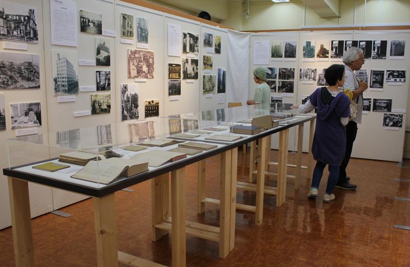 教文館3階ギャラリーステラの展示場会場の様子。中央のガラスケースには、教文館の創業について書かれてる日本美以(メソジスト)教会の年会の記録(キリスト教中央図書館所蔵)や、1898年に刊行された『創世記 詳解』(同所蔵)、教文館が所蔵する多色刷りの『クリスマスカタログ』、小冊子『コドモノオニハ』などが並ぶ=1日、教文館(東京都中央区)で