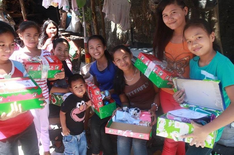 シューボックスを受け取り笑顔を見せるフィリピンの子どもたち(写真:サマリタンズ・パース)