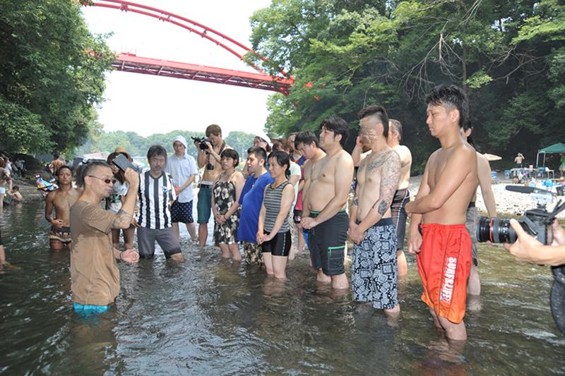 埼玉県の名栗川で行われた洗礼式の様子。バーベキューを楽しむ家族連れや若者の団体も、川で洗礼式を行うという珍しい光景にのぞきに来る人の姿もあった。