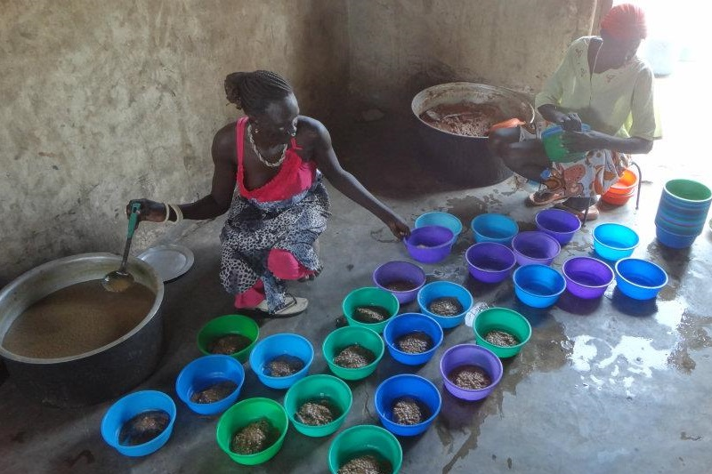 南スーダンの小学校で給食を用意する様子。この日のメニューは、ソルガム(モロコシ)の粉で作ったおかゆと豆のスープ(写真:日本国際飢餓対策機構)