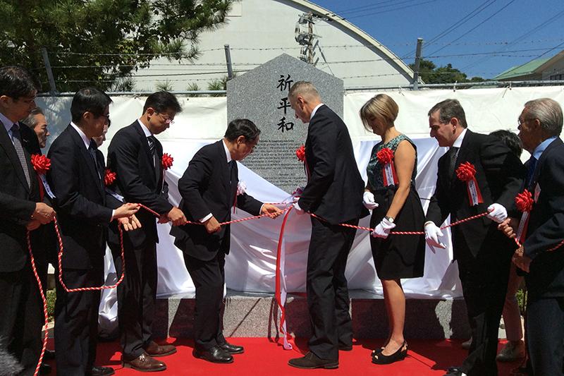 「祈平和」と刻まれた記念碑を除幕する参加者=13日、長崎市香焼(こうやぎ)町で